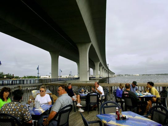 Diners have lunch at the Pelican Cafe along the St.