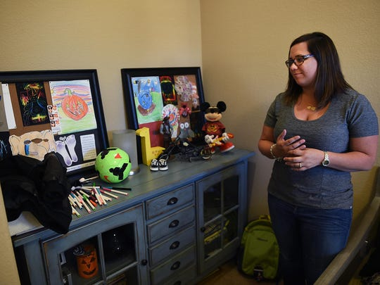 Ashley Deane looks at a collection of objects and memorabilia that belonged to her sons Jacob and Austin in her home in Sparks on April 29. Deane's children were killed by her husband, Rob, who then killed himself, in November 2014.