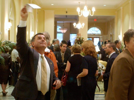 Staunton Mayor John Avoli waves to someone on the second level during the grand opening of the Stonewall Jackson Hotel on Oct. 12, 2005.