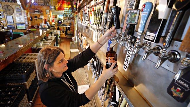 Bartender Teresa Ceretti pours a growler of Stone coffee milk stout at El Bait Shop.