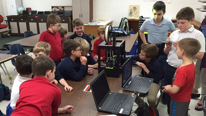 Members of the Coding Club at Trinity Lutheran School in Neenah watch a 3-D printer make a Pokemon figure. The printer is owned by the Neenah Public Library.