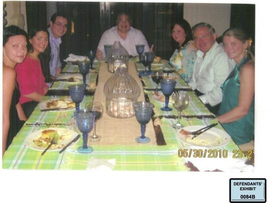 Defendants' exhibit: U.S. Sen. Bob Menendez, second from right, sits around the dinner table with Salomon Melgen, at head of table, Flor Melgen, third from right, and other family members and guests at Melgen's home in Casa de Campo, Dominican Republic. The photo is dated May 30, 2010.