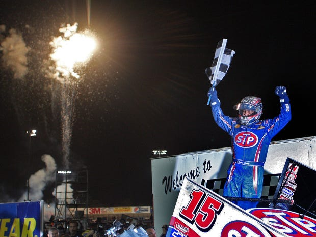 Fireworks explode in the background as Donny Schatz celebrates winning the final race at the 2012 Knoxville Nationals.