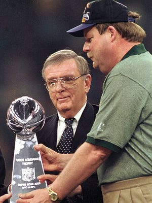 Former Green Bay general manager Ron Wolf, left, and former coach Mike Holmgren hold the Lombardi Trophy after Super Bowl XXXI in 1997. Wolf will be inducted into the Pro Football Hall of Fame in August.