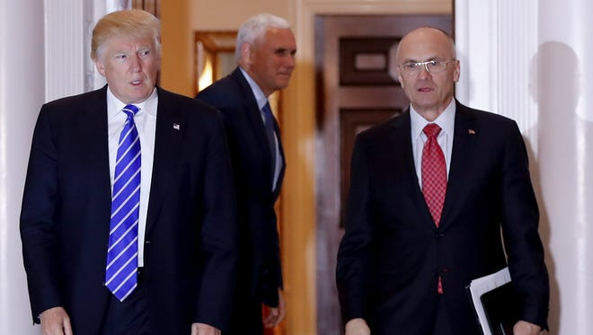 In this Nov. 19, 2016, file photo, Donald Trump walks Andy Puzder from Trump National Golf Club Bedminster clubhouse in Bedminster, N.J.