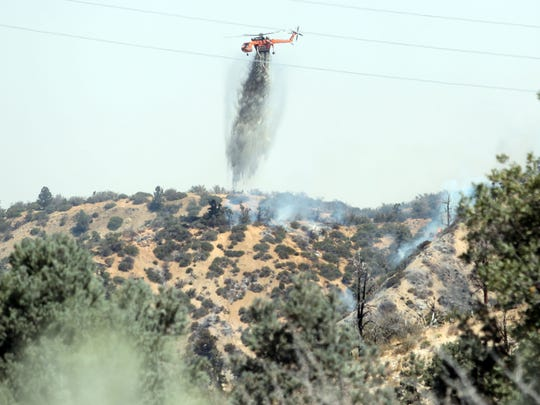 A helicopter drops water on a flare up from the Blue Cut Fire neat the eastern edge of Wrightwood, California on Aug. 18, 2016.