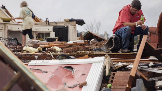 Jeff Bullard sits in what used to be his home's foyer as his daughter, Jenny Bullard, looks through debris after a tornado, Sunday in Adel, Ga.
