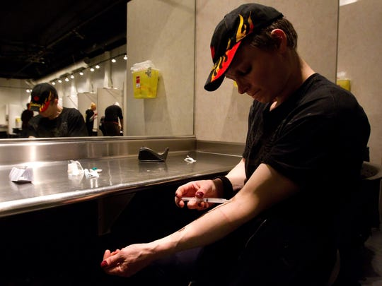 Nicole Henry injects morphine he bought on the street at the Insite safe injection clinic in Vancouver, B.C., in 2011.