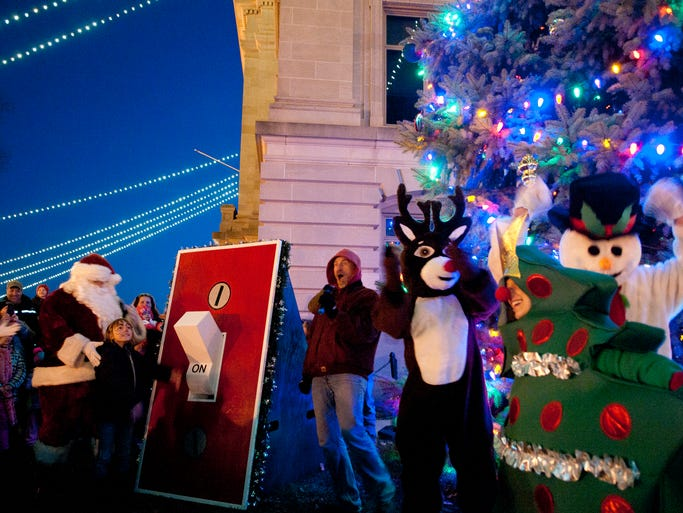 Ava Fleehearty, 8, flips the switch to turn on the lights around the Hendricks County courthouse during Christmas on the Square in Danville, Friday, Nov. 29, 2013.