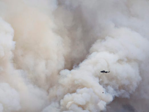 A helicopter battles a wildfire in Fort McMurray, Alberta,