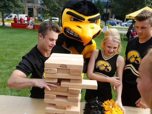 Iowa cheerleaders Adam O'Brien, left, Megan Renkel,