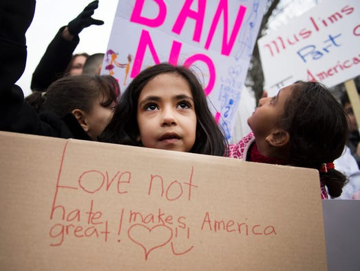 Syrian refugee Shahd Marziuk, 6, holds a sign during