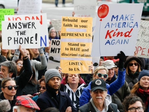 Protesters hold signs and landline phones during a