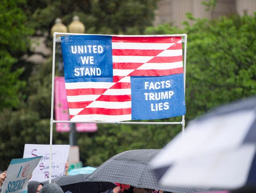 Marchers carry an American flag sign for the March
