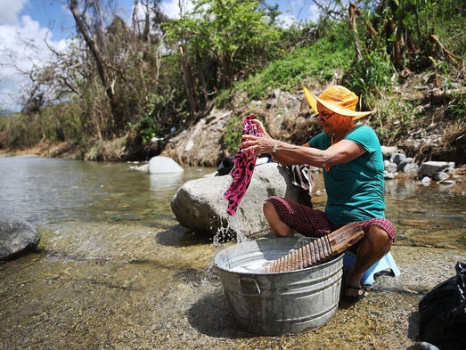 Marila Leon washes clothes in a river in the wake of