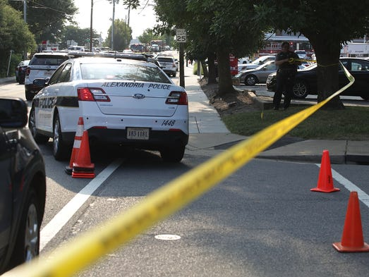 Investigators gather near the scene of a shooting in