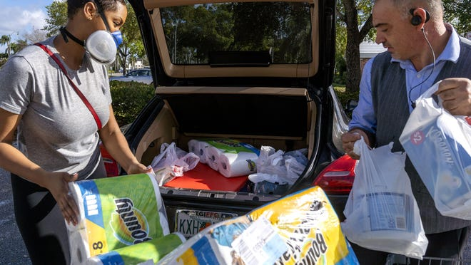 Taniesh Simpson gets help loading her car with supplies from Walgreens associate Luis DaSilva on March, 14, 2020 in West Palm Beach, Florida. Simpson will use the items at home, work and ship the rest to her sister in Georgia to help prevent the spread of COVID-19 coronavirus.