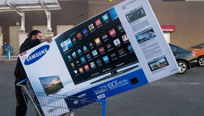 Black Friday shopper Umer Gonzalez pushes his Samsung big screen TV after purchasing it at a Walmart in Fairfax, Virginia, on November 28, 2014.