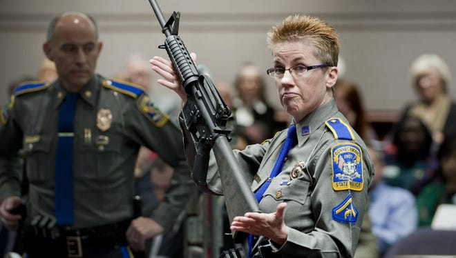 An officer holds up a Bushmaster AR-15 rifle in Hartford, Conn., in 2012.
