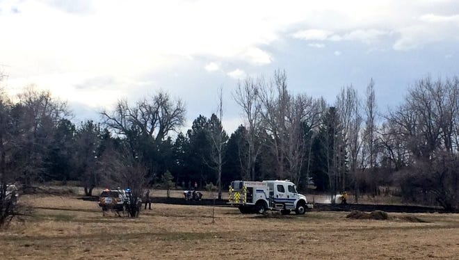 Crews mop up after a minor grass fire near Laporte Avenue and North Overland Trail on Sunday.