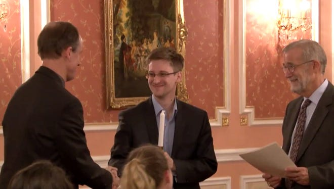 Former NSA systems analyst Edward Snowden receives the Sam Adams Award for Integrity in Intelligence this month in Moscow from former U.S. officials.