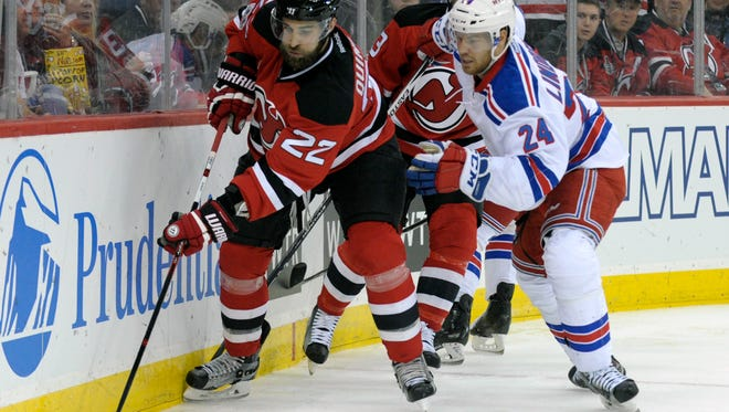 New Jersey Devils' Kyle Quincey (22) skates with the puck as he is pursued by New York Rangers' Oscar Lindberg during the first period of an NHL hockey game Saturday, Feb. 25, 2017, in Newark, N.J. (AP Photo/Bill Kostroun)