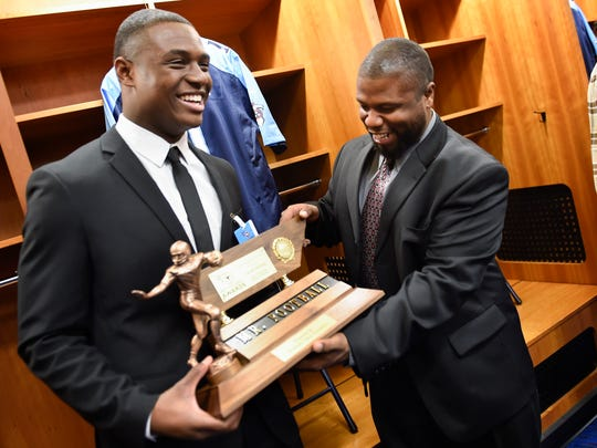 Jacob Phillips of East Nashville Magnet School laugh with his football coach Brian Waite after winning the Division 1 Class 3A 2016 Mr. Football Award Monday Nov. 28, 2016, in Nashville, Tenn.
