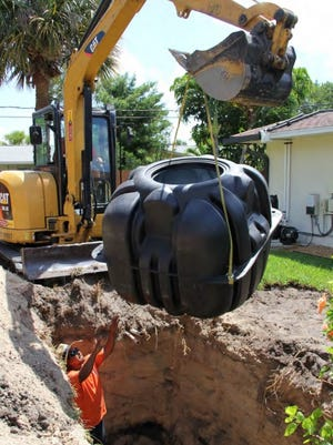 Workers from Reliable Septic and Services in Vero Beach install a hybrid septic tank system that uses a pump to convey liquid from existing septic tanks to the city's sewer plant.