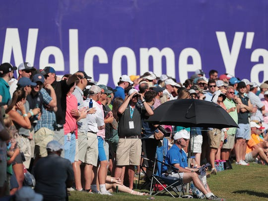 Fans watch as golfers finish up their round on the