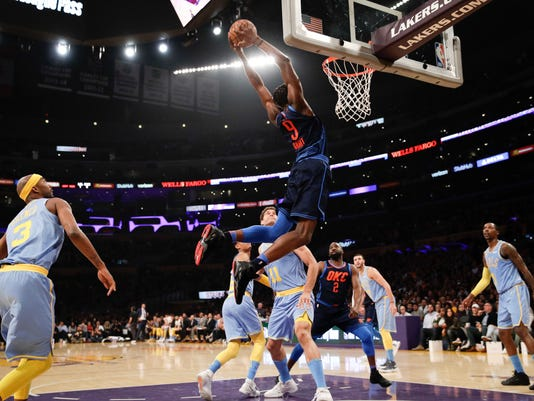 Oklahoma City Thunder's Jerami Grant, center, goes up for a dunk during the first half of an NBA basketball game against the Los Angeles Lakers, Wednesday, Jan. 3, 2018, in Los Angeles. (AP Photo/Jae C. Hong)