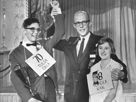 James Wagner, director of the National Spelling Bee, raises the hand of Michael Kerpan Jr., the 1965 spelling bee champion.