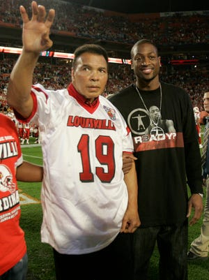 Boxing great Mohammad Ali greets Orange Bowl fans as he and Miami Heat's Dwyane Wade head to midfield for the coin toss at the Orange Bowl football game between Wake Forest and Louisville Tuesday, Jan. 2, 2007,  in Miami. (AP Photo/Pool, Lynne Sladky)