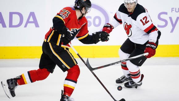 New Jersey Devils' Ben Lovejoy, right, and Calgary