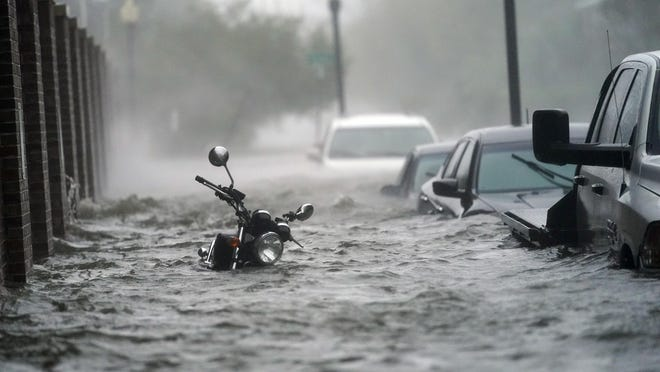 Cars and a motorcycle are underwater in Pensacola, Florida, on Wednesday as Hurricane Sally makes landfall near Gulf Shores, Alabama.