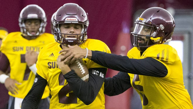 Arizona State quarterback Brady White (left) works on a ball-control drill with quarterback Manny Wilkins in practice at Verde Dickey Dome in Tempe on August 6, 2016.
