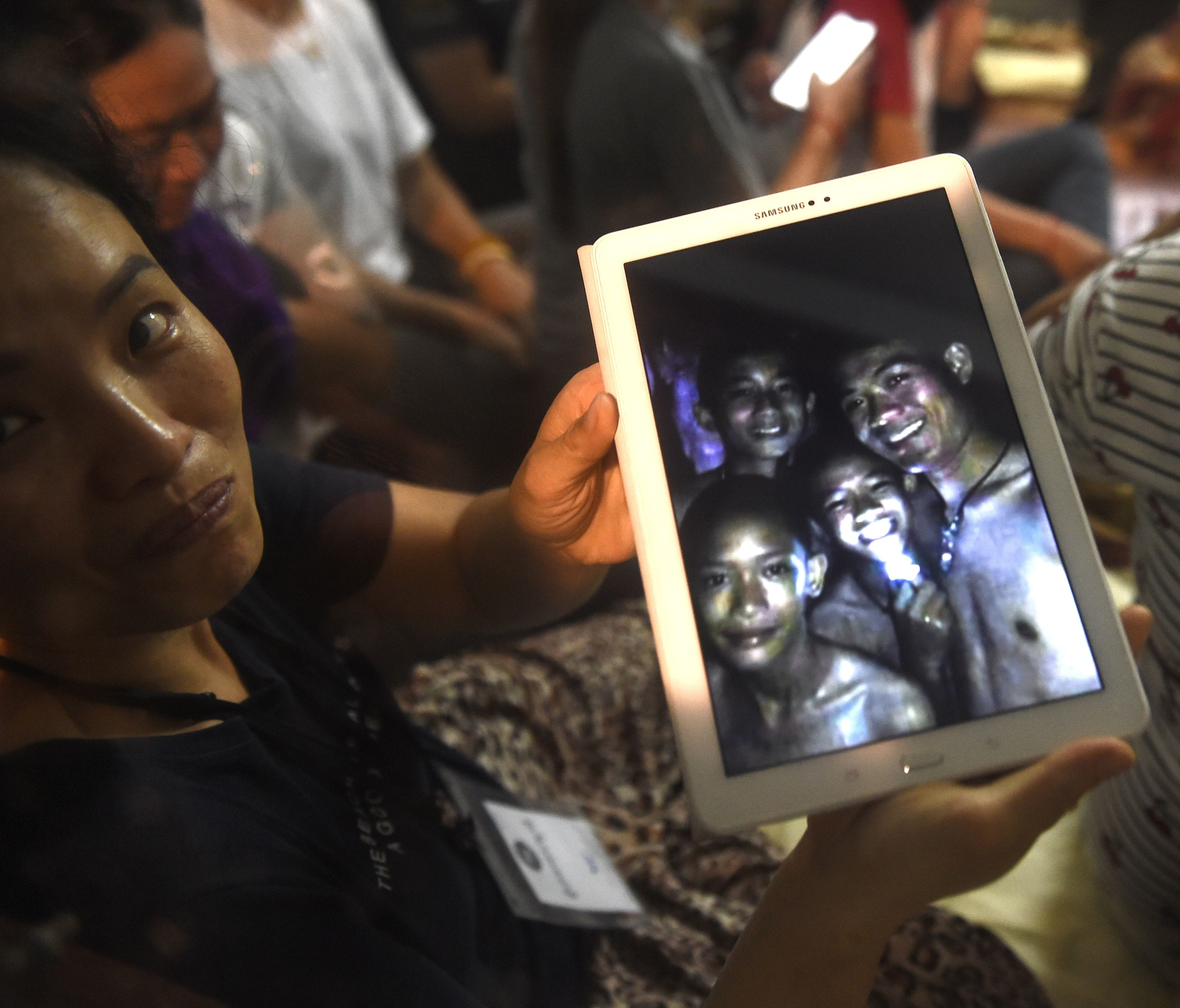 A happy family member shows a picture of four of the 12 boys that went missing inside a Tham Luang cave when all members of a children's soccer team and their coach were found alive in the cave at Khun Nam Nang Non Forest Park in the Mae Sai district