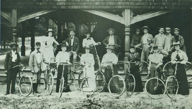 "This picture of Gay Nineties bicyclers in front of the old Glen Miller Pavilion was taken in 1894. The youths, gearing up for a Sunday ride, posed before a sign advertising (indistinct in this reproduction) ""melons on ice"" and ""hand-operated"" milkshake machines. Most of the men had mustaches. The women wore conservative long skirts prior to wearing elegantly scandalous pants beneath, called bloomers. Knickerbockers - baggy knee-length trousers worn without skirts - would later supplant bloomers and give even more unrestricted movement. Only in the 1930s did it become respectable for women to wear pants. Today's story is about mass bicycle incursions by both sexes on Main Street."