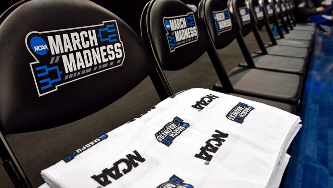A view of March Madness logos on towels and the bench during practice the day before the semifinals of the South regional of the NCAA Tournament at KFC YUM!.