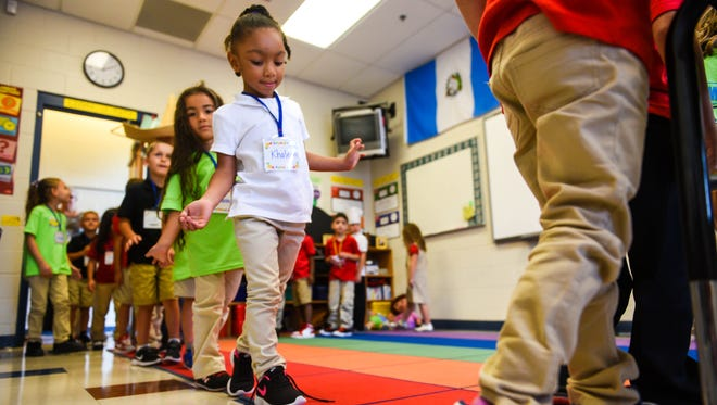 Kindergarten students make their way to Spanish class during the first day of school at Dr. William MenniesElementary School on Tuesday, September 6.