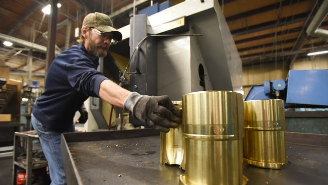 Craig Wickham reaches for a mold to put it in a CNC five-axis maching center at Anchor Glass' mold shop in Zanesville.