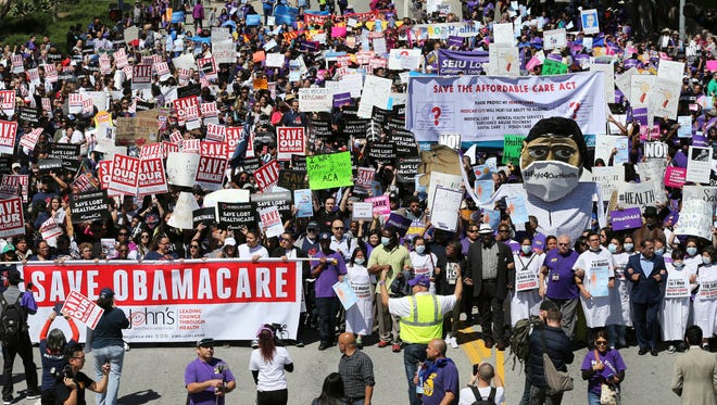 Hundreds of people march through downtown Los Angeles protesting President Trump's plan to dismantle the Affordable Care Act, also known as Obamacare, on  Thursday.