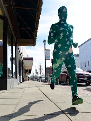 Sonny Workman of Fremont runs around Fremont dressed up in a shamrock running suit as part of an early St. Patrick's Day celebration.