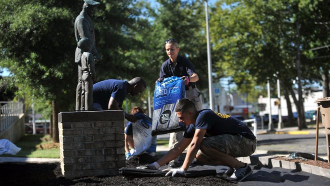 Vineland Police Sgt. Shane Harris, Police Explorer Jazlyn Roman, 16, Officer Carolina Gonzalez, and Police Explorer Joseph Torres, 17, (from left), work together on upgrades to the department's monument garden, Tuesday, Aug. 23, 2016 in Vineland.