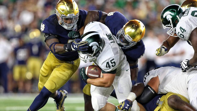 Sep 17, 2016; South Bend, IN, USA;  Michigan State Spartans fullback Prescott Line (45) is tackled by Notre Dame Fighting Irish linebacker Nyles Morgan (5) during the first half a game at Notre Dame Stadium. Mandatory Credit: Mike Carter-USA TODAY Sports