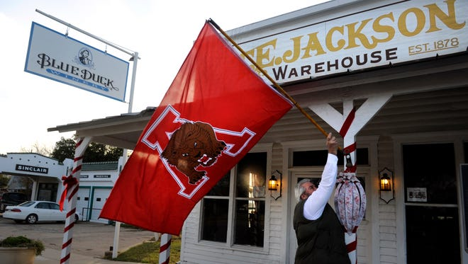 Adrian Allen, a co-owner of Blue Duck Winery in Albany, hangs a Lions flag Thursday in support of the football team. The undefeated Lions play undefeated Muenster in the Class 2A Division II regional finals Friday in Iowa Park.