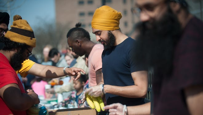 Jasdeep Glamour, of Philadelphia, distributes food to passersby on Martin Luther King Blvd. in Camden, N.J. on Saturday, April 14, 2018. Volunteers from the Sikh Coalition come from throughout Pennsylvania and New Jersey to distribute food and clothing at this location every month.