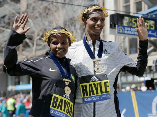 Atsede Baysa, left, and Lemi Berhanu Hayle, both of Ethiopia, pose for photos after they won the women's and men's divisions of the 120th Boston Marathon.