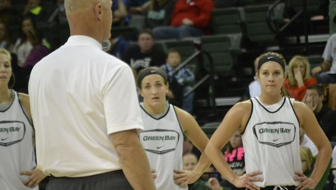 Freshman guards Jen Wellnitz, center, and Laken James, right, listen with teammates on the court as coach Kevin Borseth addresses the crowd at the end of the University of Wisconsin-Green Bay women's basketball preseason scrimmage at UWGB's Kress Events Center on Saturday, Oct. 25, 2014.