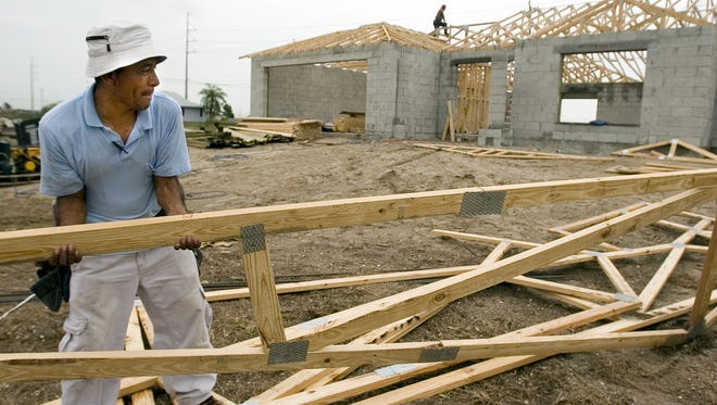FILE: Manuel Leodegario carries some  roofing material during the construction of a new house in north Cape Coral.