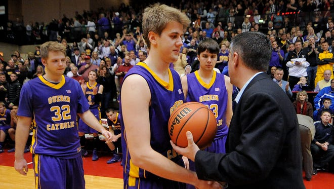 Guerin Catholic forward Aaron Brennan is presented with the game ball after losing to Greensburg during the Class 3A Semistate game, Saturday, March 22, 2014, inside the Tiernan Center at Richmond High School. Greensburg won the game 74-67.